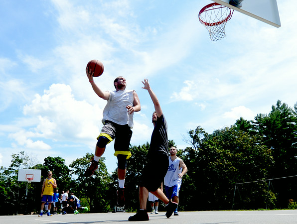 JIM VAIKNORAS/Staff photo Curran O'Connor drives to the hoop on Matt Talbot  in the TheCarriageTownThrowDown Saturday at Amesbury Park. Proceeds from the 3 on 3 basketball tournament went to the  Amesbury Educational Foundation.