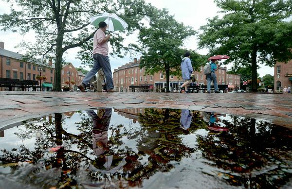 JIM VAIKNORAS/Staff photo People walk with umbellas through Market Sqaure Newburyport on a wet Fourth of July.