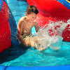 BRYAN EATON/ Staff Photo. Jacob Mahoney, 7, of Amesbury cools off going down the giant waterslide yesterday afternoon. He was at the Boys and Girls Club in Salisbury.