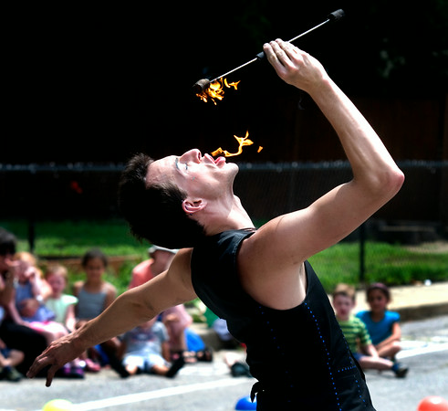 JIM VAIKNORAS/Staff photo Benjamin Reynolds eats fire as he entertains the crowd at the YWCA Summer Fun Series at the Childrens Center on Pond Street in Newburyport Thursday. Reynolds perform thrilling acts of pyrotechics including eating, breathing, and twirling fire.