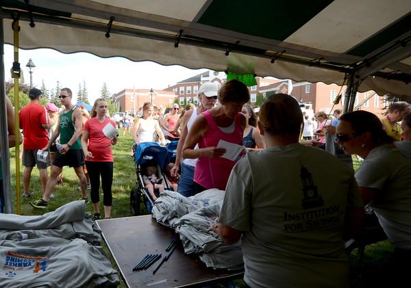 JIM VAIKNORAS/Staff photo <br /> Runners register for the Yankee Homecoming race at Newburyport High School Tuesday night.