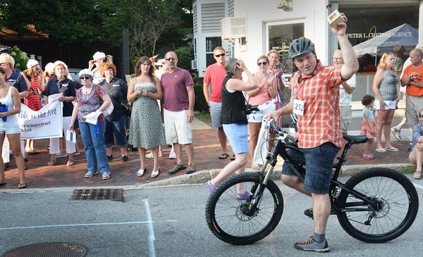 BRYAN EATON/Staff Photo. Alex Dardinski hoists his Rusty Spike trophy winning the VIP category of the Slow Bike Race.