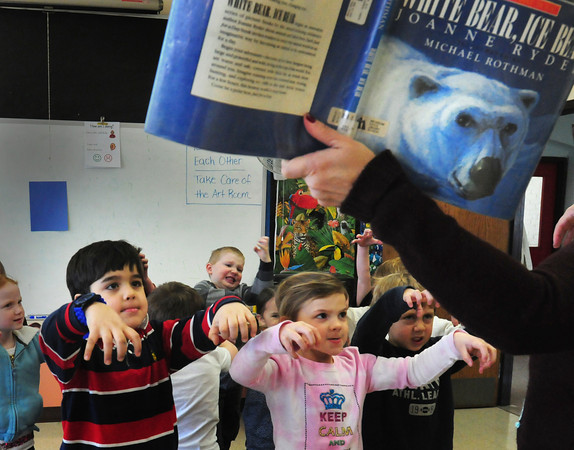 """Newburyport: Brown School first-graders in Newburyport make believe they're polar bears as art teacher Pam Jamison reads """"White Bear, Ice Bear"""" to them on Tuesday morning. Later the children drew pictures of the arctic creatures. Bryan Eaton/Staff Photo"""