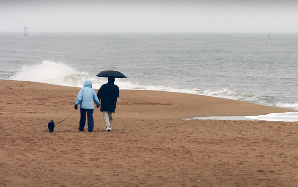 Newbury: Dog walkers head north from Plum Island Beach center on Monday afternoon as some rain started to drop. Bryan Eaton/Staff Photo