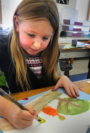 """Amesbury: Second-graders at the Amesbury Elementary School were assigned to draw a landscape on Tuesday using watercolors. Kendall Sommer, 7, chose to draw a summer landscape with a maple tree, """"a big red apple"""" and a yellow flower. Bryan Eaton/Staff Photo"""