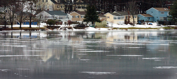 Amesbury: Homes along Whitehall Road in Amesbury reflect in melted ice on Lake Gardner as temperatures were in the 50's on Monday with rain falling. The water will refreeze as cold weather is returning today and tomorrow with another round of above average temperatures for the weekend. Bryan Eaton/Staff Photo
