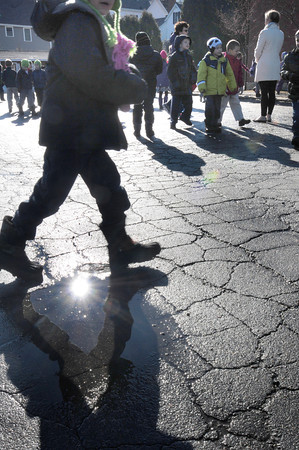 Amesbury: Sunlight reflects off a puddle as children play at recess at Amesbury Elementary School on Wednesday in above normal temperatures. The weather is still warm today though there may be a little snow this weekend, Bryan Eaton/Staff Photo