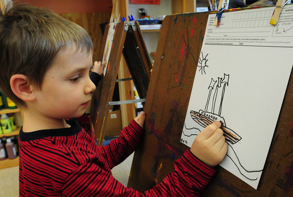 """Newburyport: Ben Misner, 5, colors in a ship he drew in Pam Jamison's art class at the Brown School on Tuesday. Theme of the project is """"Sailing In to the New Bresnahan School"""" which opens in the fall. The artwork from the children children will be copied onto ceramic tiles and placed permanently in the new school's lobby. Bryan Eaton/Staff Photo"""