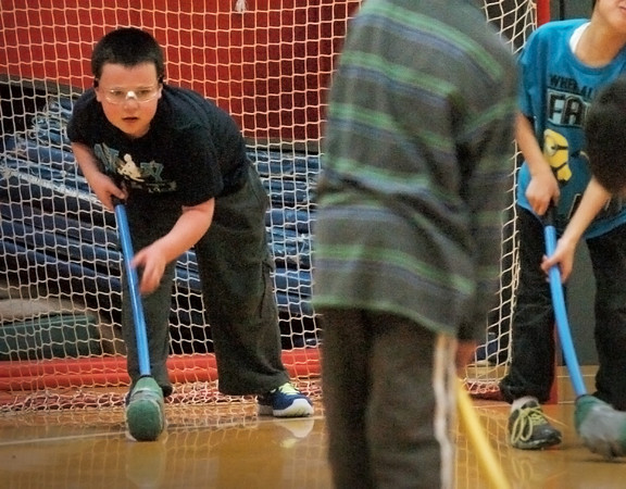 Amesbury: Jean Paul Collins is proned to make a save in a game of floor hockey on Wednesday afternoon. The youngster was in Ted Flaherty's phys ed class at the Cashman School in Amesbury. Bryan Eaton/Staff Photo