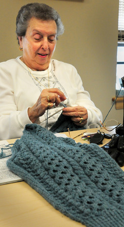 """Amesbury: Mae Kelleher works on knitting a sweater at the Amesbury Senior Center on Tuesday morning in the activity """"Busy Needles."""" The participants make sweaters, hats and scarves for different agencies who distribute them to needy children. Bryan Eaton/Staff Photo"""
