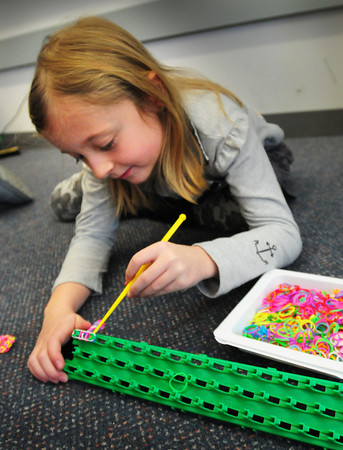 Salisbury: Madison January, 7, spreads small, colored rubber bands on a template as she makes a fishtail bracelet on Wednesday in Laura Savey's class. She was making the bracelets during recess, which was held indoors,  at Salisbury Elementary School. Bryan Eaton/Staff Photo
