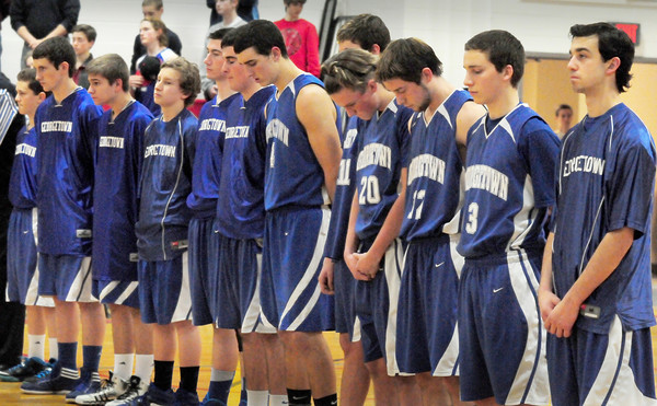Amesbury: Members of the Georgetown High basketball team lead a moment of silence last night, before taking on Amesbury High, in remembrance of their former coach Mike Rowinski who passed away yesterday. Bryan Eaton/Staff Photo