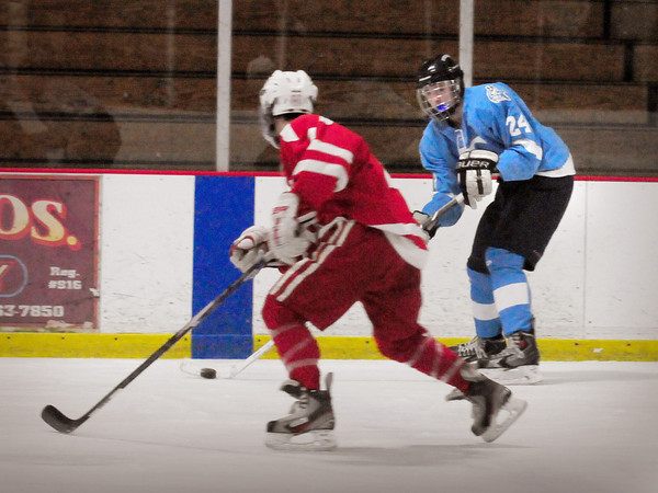 Newburyport: Triton forward Kyle Hillick moves the puck down the ice as a Saugus player moves in. Bryan Eaton/Staff Photo