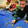 "Newburyport: Youngsters at the Newburyport Montessori School grab small fish laid out on a blue tarp representing the ocean to give to classmates holding baby penguin dolls to ""feed."" Staff from Mass. Audubon's Joppa Flats Education Center were at the school teaching about the different kinds of penguins and how they live. Bryan Eaton/Staff Photo"