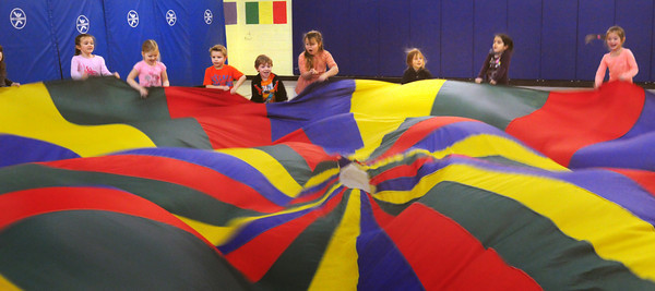 """Amesbury: Kindergartners in Christopher Dodier's phys ed class played several games with a parachute on Wednesday. Here they played """"alligator"""" where two students would go under and grab the feet of others to """"pull them under."""" Bryan Eaton/Staff Photo"""