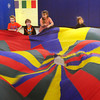 "Amesbury: Kindergartners in Christopher Dodier's phys ed class played several games with a parachute on Wednesday. Here they played ""alligator"" where two students would go under and grab the feet of others to ""pull them under."" Bryan Eaton/Staff Photo"