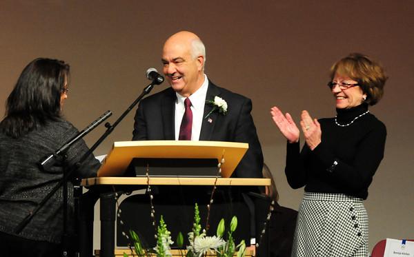 Amesbury: Donna Gray applauds as her husband Ken Gray was publicly sworn in as Amesbury mayor by city clerk Bonnijo Kitchin last night at Amesbury High School. Bryan Eaton/Staff Photo