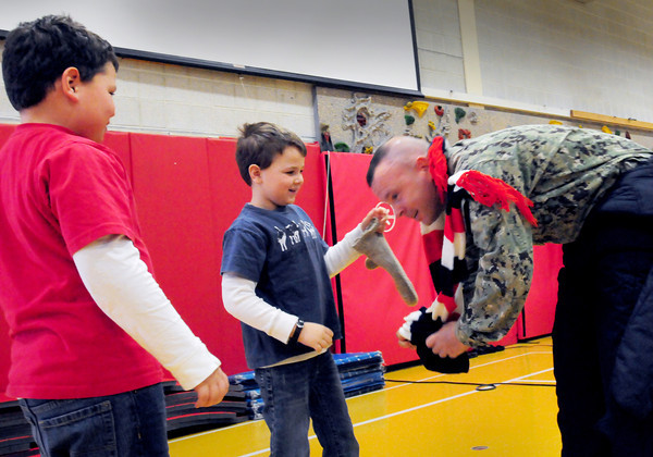 """Amesbury: Garrett Bailey, 6, with brother Jackson, 8, left, takes the gloves and scarf off of """"Officer Ralph"""" in front of the Cashman School body not knowing it's his father, Amesbury police Sgt. Craig Bailey, who just returned from US Coast Guard service in Cuba. Bryan Eaton/Staff Photo"""