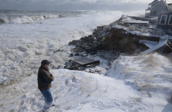 Newbury: John Rossi looks at the damage caused to his mother in law Helen Dolberg home at 35 Southern Blvd on Plum Island Friday morning. Jim Vaiknoras/staff photo