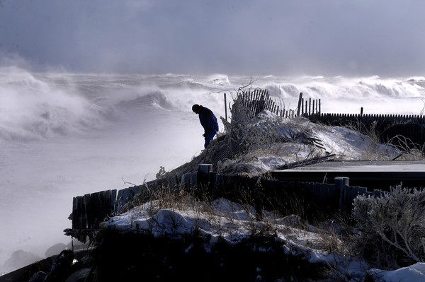 Newbury: A Southern Blvd resident on Plum Island watch as waves at high tide pound the shore. Jim Vaiknoras/staff photo