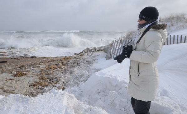 Newbury: Sadie Dayton of Plum Island takes some photographs of the high surf at the beach center Friday morning at high tide. Jim Vaiknoras/staff photo