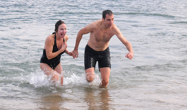 Salisbury: Karen and Ed Kinnaly run out of Ocean at Salisbury Beach after the two ran in the 33rd annual Hangover Classic Wednesday morning. Dispite the cold weather many of the runners took the plunge in the frigid water. jim Vaiknoras/staff photo