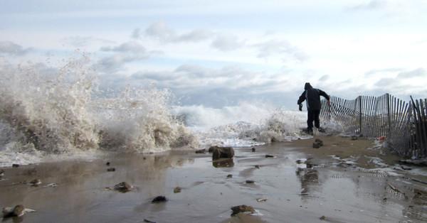 Salisbury:Paul Waterman of Salisbury hunches over as a wave blasts into the dune at Salisbury Beach Center. <br /> John Macone/staff photo