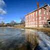 Newburyport: Essex Superior Court house is reflected in the melting ice of the Frog Pond at the Bartlett Mall Sunday morning. After last weeks deep freeze, the warm weather has turned the area into mud and slush.the annual Winter Carnival that was planned for this past Saturday  was postponed till January 25th due to the warm weather. Jim Vaiknoras/staff photo