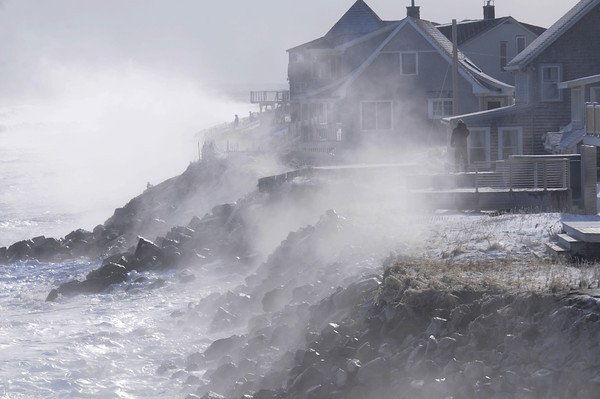 Newbury: Residence on Southern Blvd on Plum Island watch as waves at high tide pound the shore. Jim Vaiknoras/staff photo