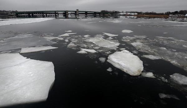 JIM VAIKNORAS/Staff photo Ice broken up in the warmer weather flows down the Merrimack River past the Gilllis Bridge in Newburyport.