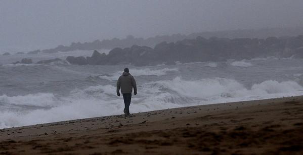 JIM VAIKNORAS/Staff photo A man walks down Plum Island Beach on a warm foggy day Sunday.
