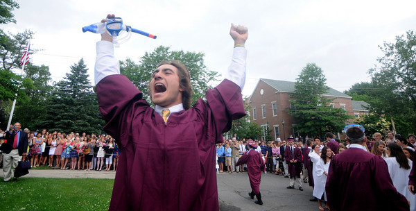 """Byfield: Cody Ferriero of Essex Ma. celebrates after jumping the wall, a tradition at the Governor's Academy Commencement. Cody and some of his fellow graduates donned snorkles and flippers to make the leap as """" protection"""" from the rain. Jim Vaiknoras/Staff photo"""