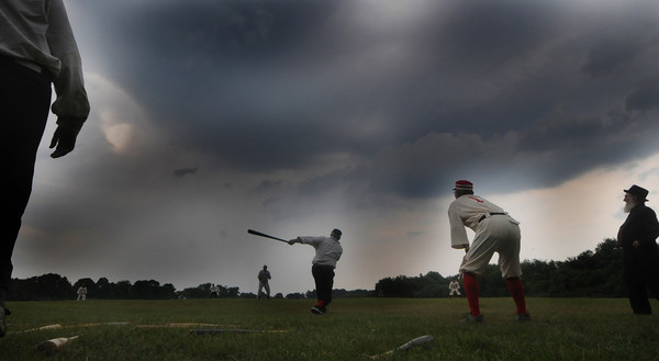 Newbury: An Essex player gets a hit off Ipswich as thunder clouds roll in during their game of 1861 rules baseball at the Spencer-pierce Little farm in Newbury Sunday. Jim Vaiknoras/Staff  photo