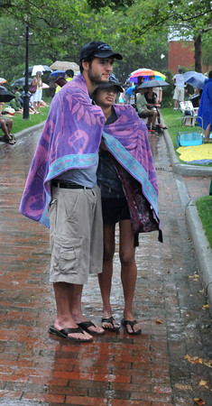Newburyport: Rick Carrick of Wakefield and Miera Patel of California stand in the rain as they listen to the Candles perform at the Riverfront Festival in Market Landing Park in Newburyport Saturday. Despite the rain, which finally ended, the day long event continued through the early evening. Jim Vaiknoras/Staff photo