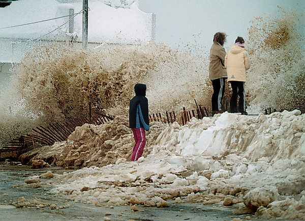 Nancy Riley-Whitehill, her daughter tyler Whitehil, and a friend Kaitlin Bishop watch the high surf at Slisbury beach center as a unexpected wave breaks in front of them.<br /> jim Vaiknoras photo. 1/4/2003.