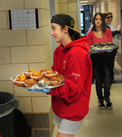 """Amesbury: Brianna Duchemin, 14, left, and Hannah Locke, 16, deliver muffins to the Amesbury Council on Aging as a snack after the senior citizens finished their games of bingo on Tuesday. The two are in the Amesbury Public Library's Summer Reading Program """"Teens Can Make a Difference."""" Bryan Eaton/Staff Photo"""