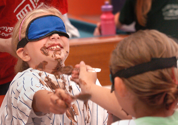"""Salisbury: Abbey Lewan, 8, has more chocolate pudding on her face than in her mouth as she and Noel Allen, 9, back to camera, try to feed themselves blindfolded. The event was one of the weeks theme """"Ooey Gooey"""" at the Boys and Girls Club in Salisbury. Bryan Eaton/Staff Photo"""