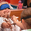 "Salisbury: Abbey Lewan, 8, has more chocolate pudding on her face than in her mouth as she and Noel Allen, 9, back to camera, try to feed themselves blindfolded. The event was one of the weeks theme ""Ooey Gooey"" at the Boys and Girls Club in Salisbury. Bryan Eaton/Staff Photo"