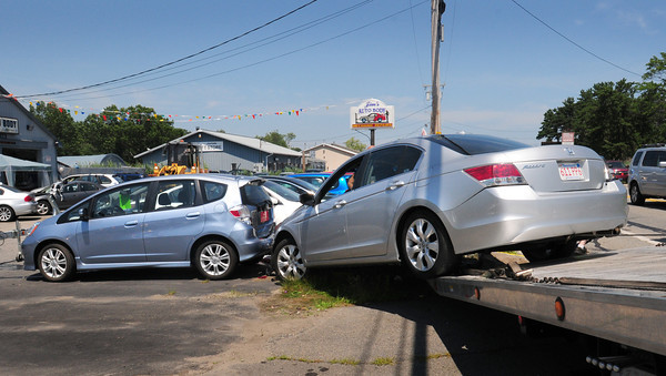 Salisbury: One car involved in a three vehicle crash, which also hit these parked cars at Jim's Auto Body on Bridge Road in Salisbury, is loaded onto a flatbed tow truck yesterday afternoon. Bryan Eaton/Staff Photo