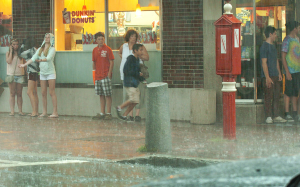 Newburyport: Youngsters took cover under the Richdale store awning during yesterday's heavy rainfall. Some people were seen walking in their bare feet to keep their footwear dry. Bryan Eaton/Staff Photo