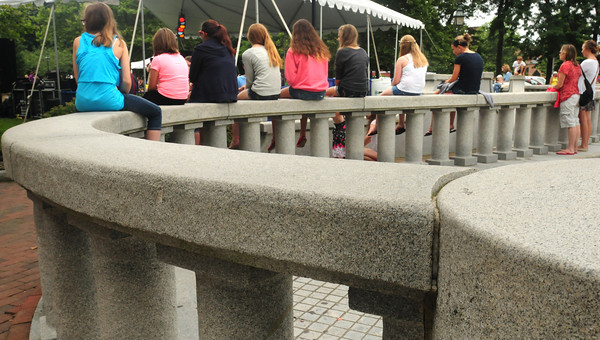 Newburyport: Youngsters sit on the granite fencing at Newburyport's Waterfront Park catching some of the acts at the Yankee Homecoming Kids Talent Showcase. Bryan Eaton/Staff Photo