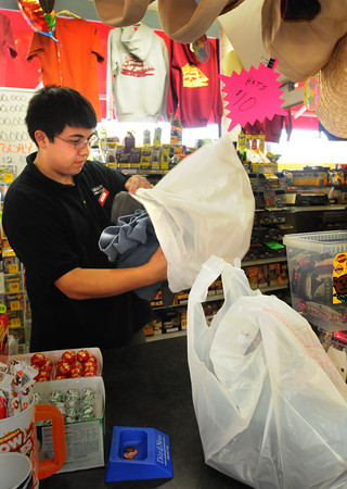 Newburyport: Richdale clerk Xander Ing of West Newbury stuffs two sweatshirts into plastic bags at the Newburyport store which sells lots of clothing with Newburyport stamped on them for tourists and locals. A proposal is underway to ban such bags. Bryan Eaton/Staff Photo
