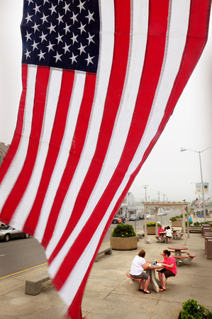 Salisbury: A northeast wind blew the flags around at Salisbury Beach Center keeping the handful of visitors on the cool side. Fourth of July and the following weekend will be a different story as temperatures flirt with the 90's with lots of sun making beach-goers and merchants alike happy. Bryan Eaton/Staff Photo