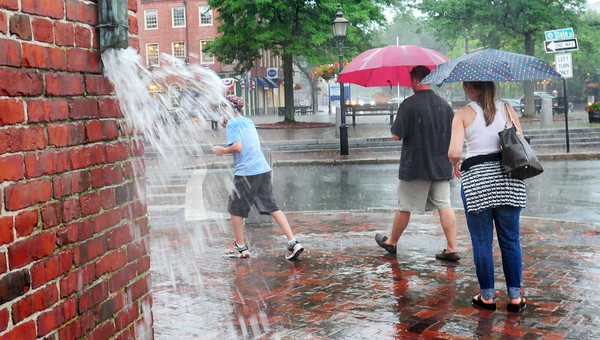 Newburyport: People without umbrellas scurried for cover as the sky opened up in a deluge of rain yesterday, here at the corner of State and Liberty Streets in Newburyport. Bryan Eaton/Staff Photo