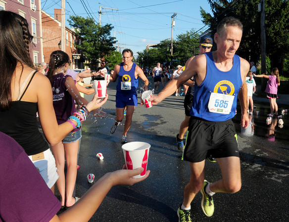 Newburyport: Teens hand off water to runners in the Yankee Homecoming 10 Mile Road Race as they run past the Starboard Galley on Water Street. Bryan Eaton/Staff Photo