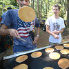 Amesbury: Jack Plante looks on as David Hodge flips a flapjack Pancakes in the Pines in Amesbury Thursday morning. Jim Vaiknoras/staff photo