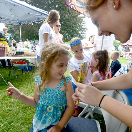 Newburyport: Keara McBride, 4, looks at her face after it was painted by Georgetown high cheerleader Kelly Guyer at Old Fashion Sunday. Jim Vaiknoras/staff photo