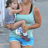 newburyport: Stephanie Powell carries her daughter Olivia, 4, to the finish  of the Yankee Homecoming 5k Tuesday night. Jim Vaiknoras/staff photo
