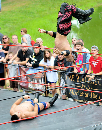 """Newburyport: Atlantic Pro Wrestler the International Super Star flies off the ropes at Mark """"The Sure Thing"""" Shurman during their match at Old Fashioned Sunday. Jim Vaiknoras/staff photo"""