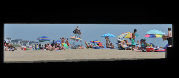 Salisbury: Brightly colored umbrellas, are framed by the foundation under Seaglass, as they dot the the sand on Salisbury Beach Sundy morning. Jim Vaiknoras/staff photo
